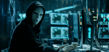 Hacker in mask sitting at a computer