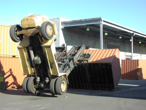 Picture of a forklift turned upside down, picking up a shipping container.