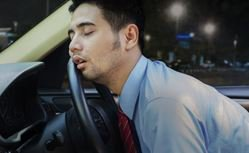 A man asleep on his steering wheel