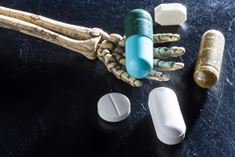 A picture of a skeleton hand holding a pill in an open palm