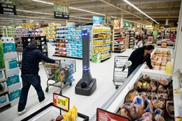 A photo of a robot on wheels going through the aisles of a grocery store