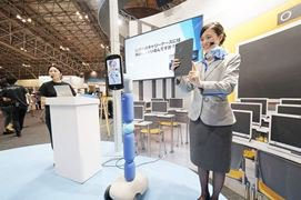A woman standing next to a device on wheels with her face on it, showing an example of telepresence robots