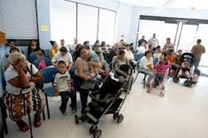 A photo of a crowded waiting room at the doctor's office, with many families sitting around