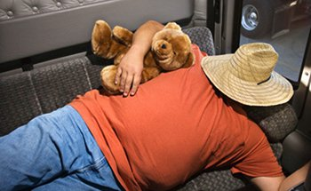 A man cuddling with a teddy bear with a hat pulled over his head, sleeping in the space above a truck