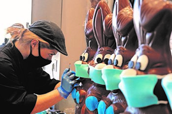 a woman putting fondant masks on chocolate easter bunnies